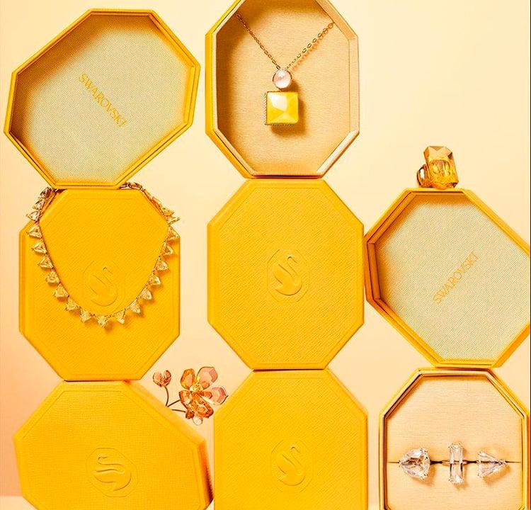 Vários pacotes octogonais amarelos um em cima do outro. Alguns estão abertos e mostram colares e anéis da Swarovski.