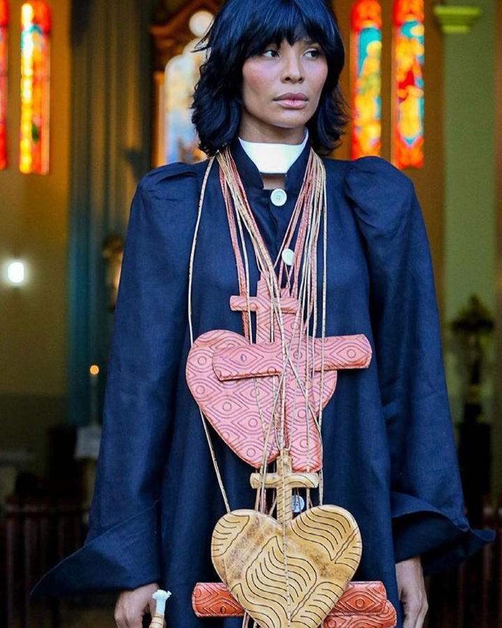 A modelo Suyane Moreira com uma jaqueta azul marinho e colares grandes em formato de coração.
