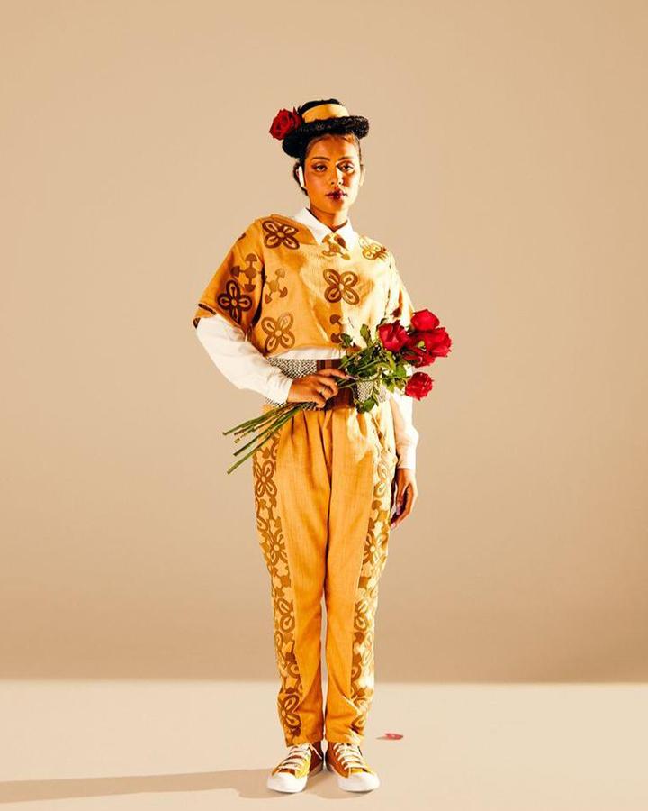 Modelo com blusa e calça amarelas, um chapéu, e segurando flores.