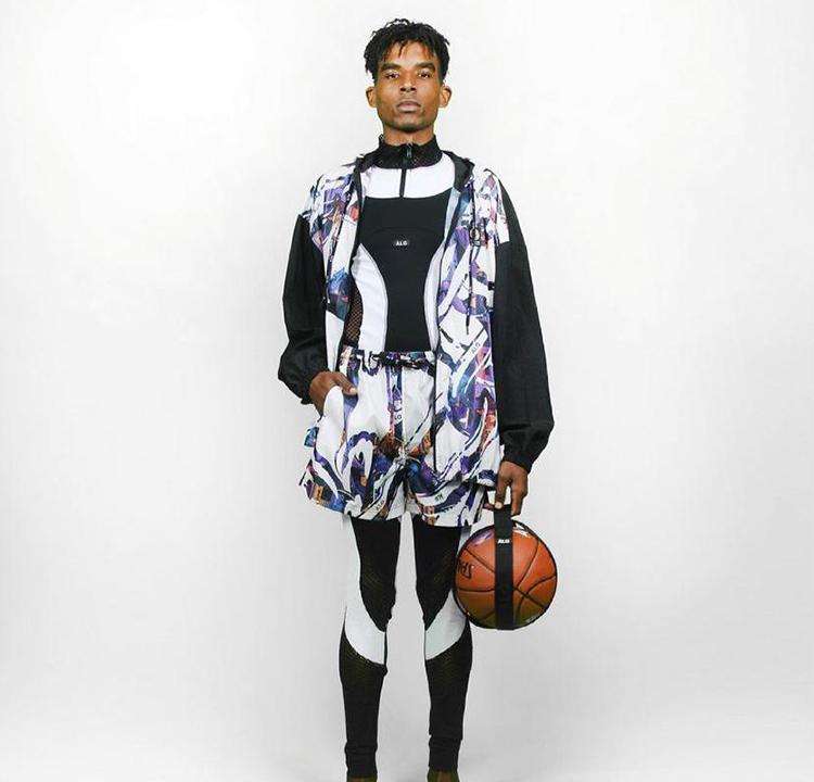 Modelo com roupa atlética preta e short e colete coloridos por cima.