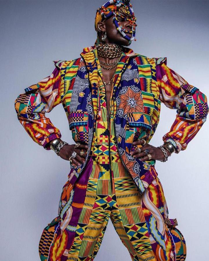 Modelo masculino com terno colorido e estampado, e acessórios no pescoço e cabeça.