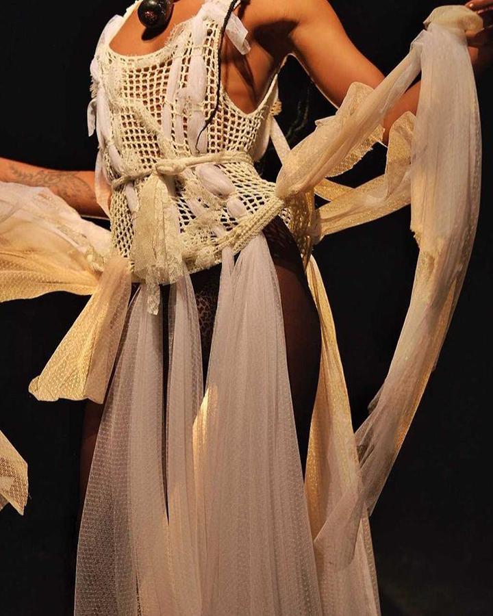 Vestido branco feito de crochê, nós e tecidos esvoaçantes.