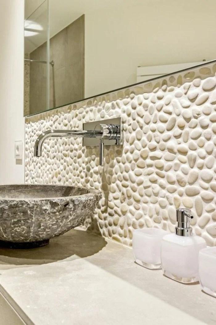 Banheiro com seixo acima da pia.