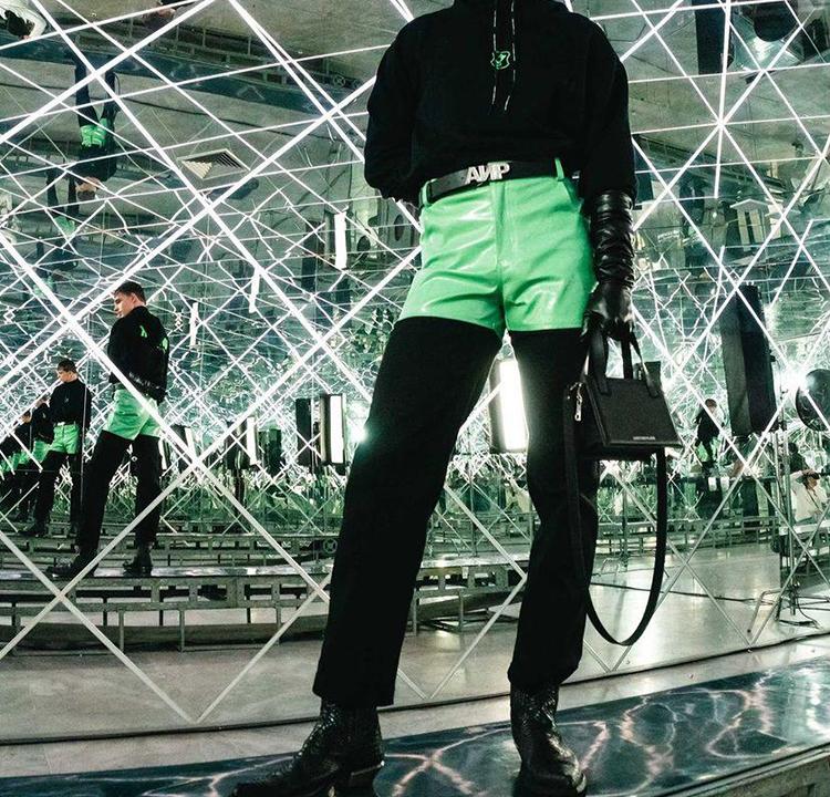 Modelo de roupa preta e short verde vivo por cima.