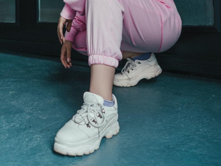 Foto de jovem usando tênis branco.