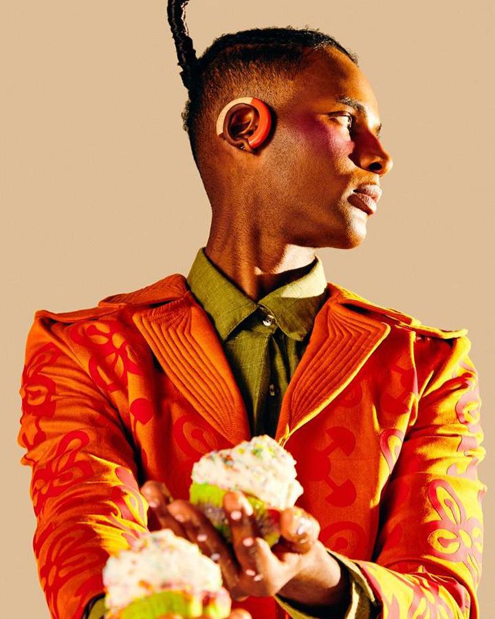 Homem com blusa de botão verde e terno laranja.