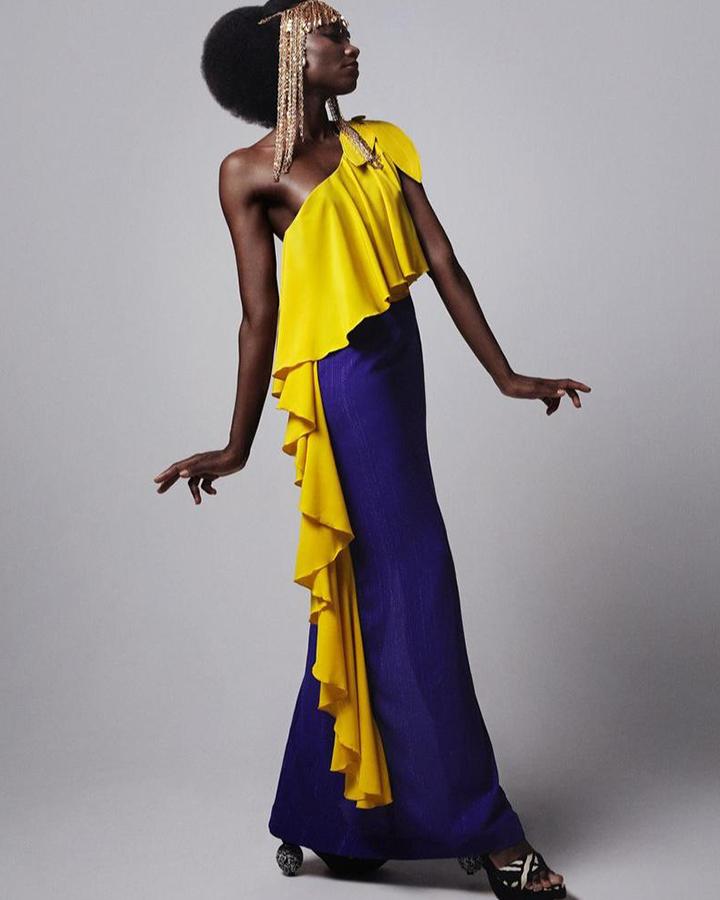 Modelo com vestido longo azul e amarelo.