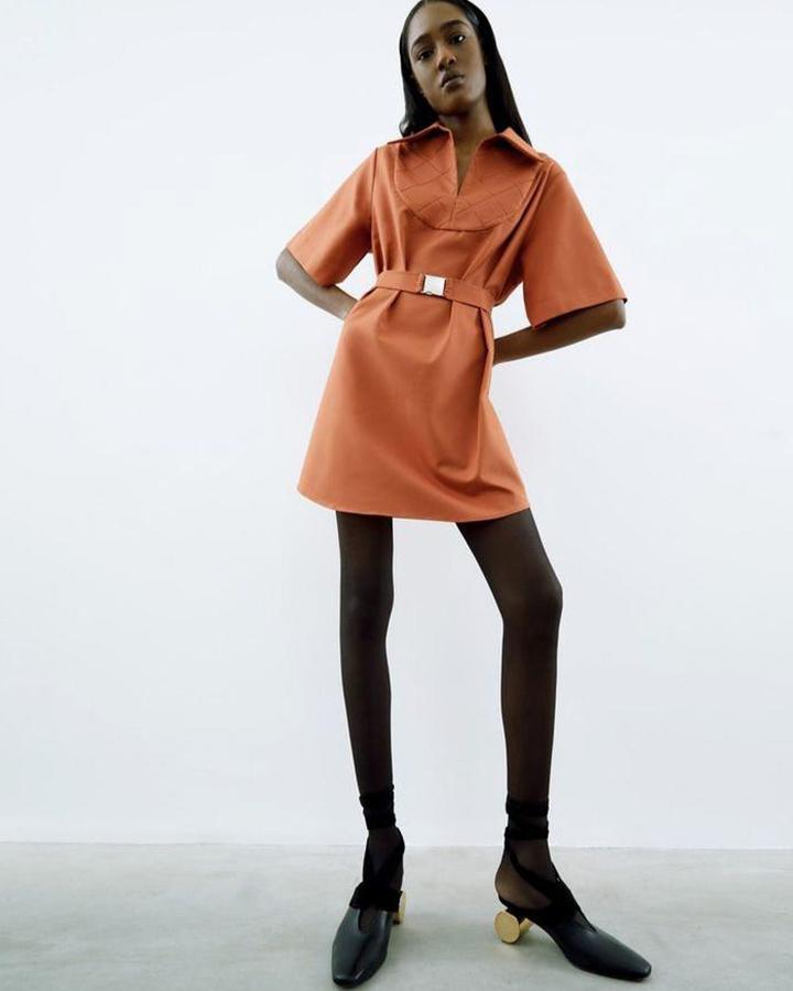 Modelo em vestido curto marrom e meia calça preta.