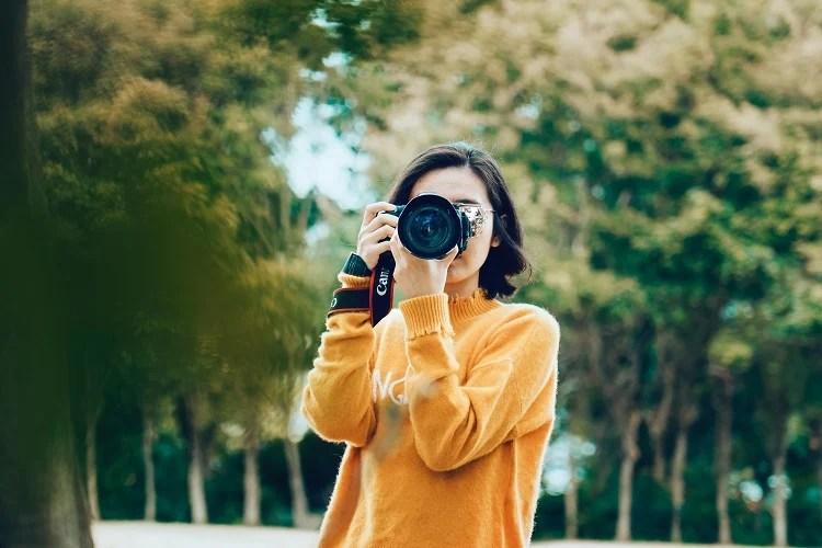 Foto de mulher de blusa amarela segurando uma câmera fotográfica na altura dos olhos
