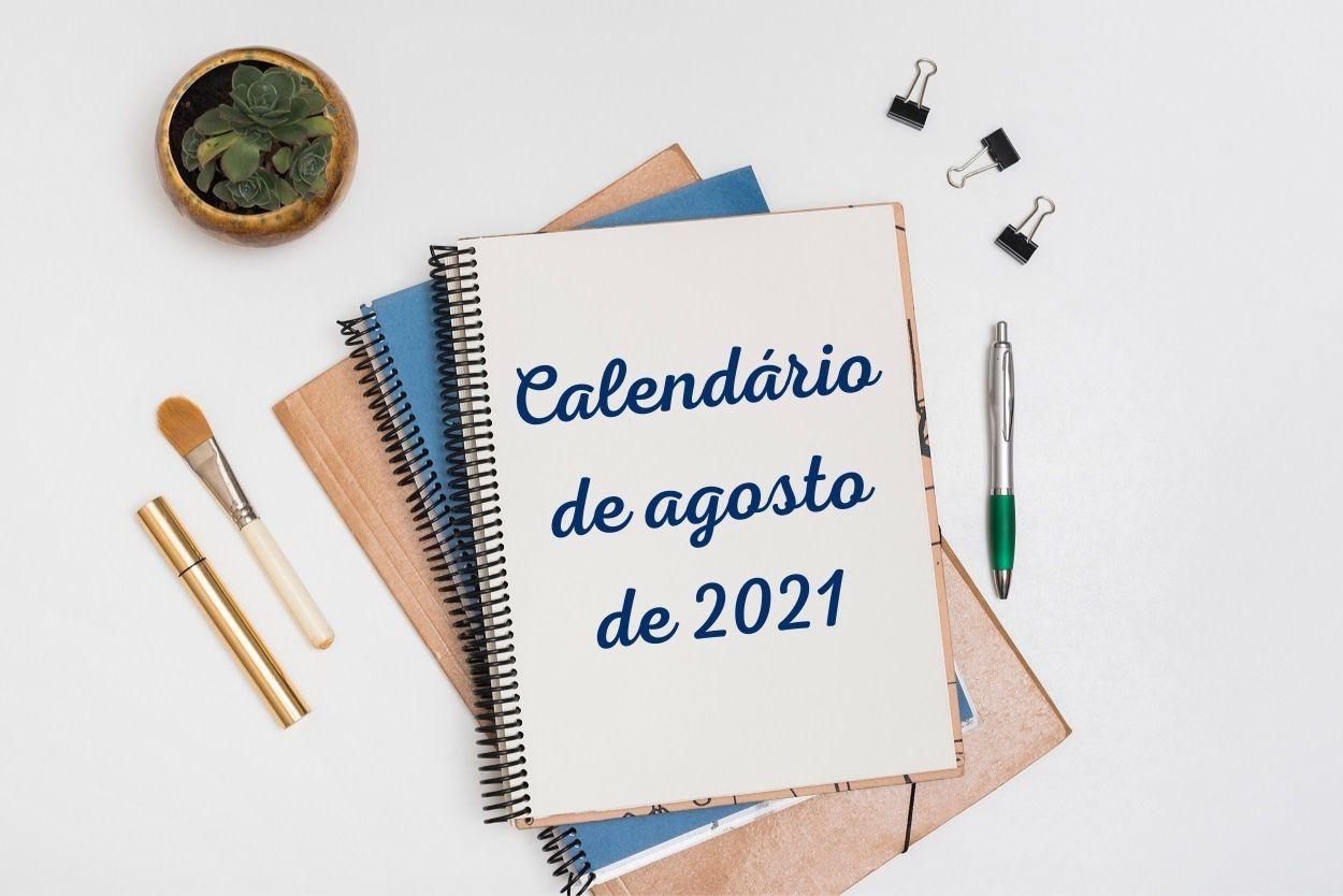 """Foto de mesa branca com itens de escritório e caderno onde está escrito """"calendário de agosto de 2021"""""""