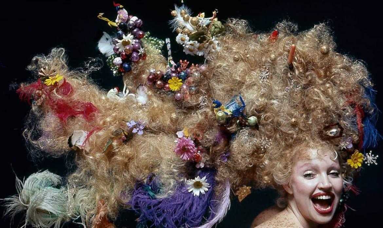 Elke Maravilha posando sorrindo com um sorriso aberto, com o cabelo loiro muito longo e armado, enfeitado com inúmeros objetos.