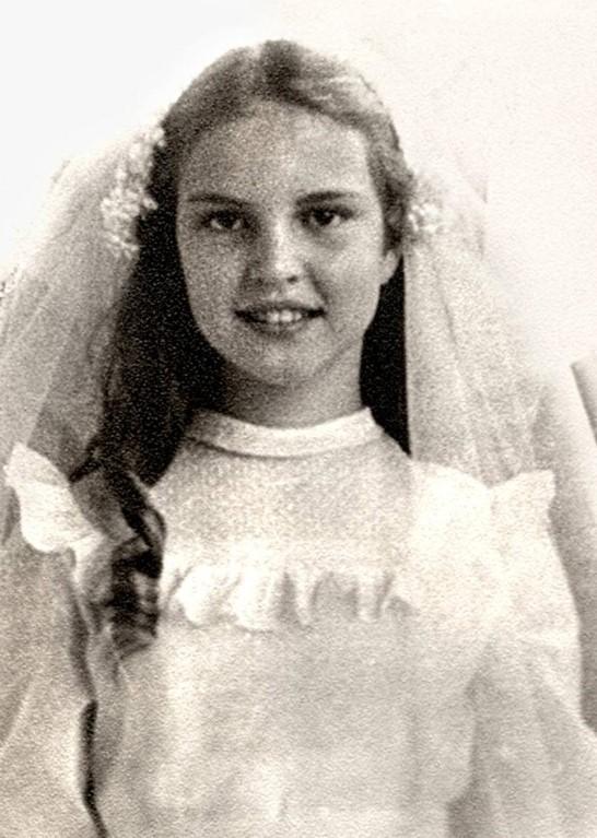 Retrato em preto e branco de Elke Maravilha quando criança, sorrindo, com um vestido branco com babados e um véu branco preso ao cabelo.