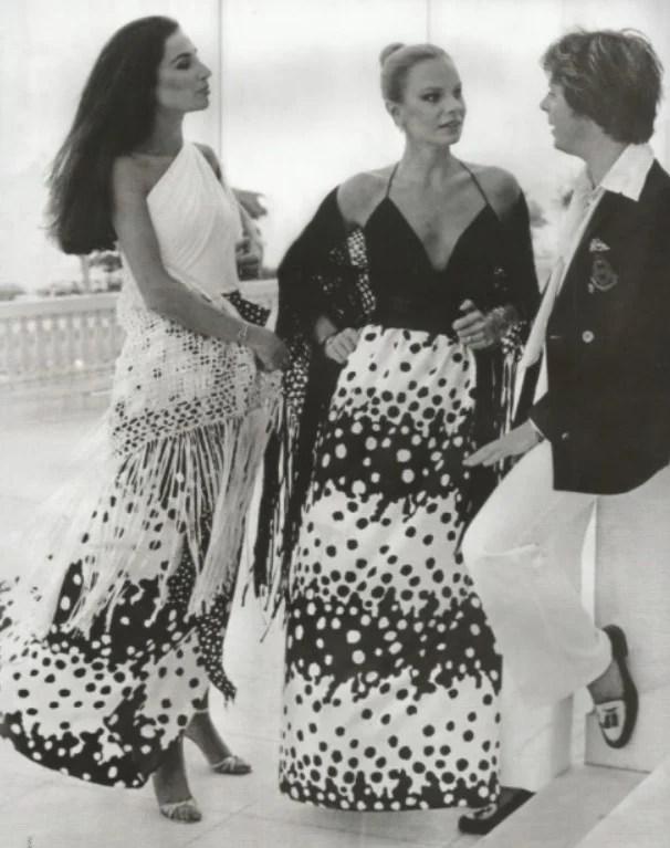 Imagem em preto e branco do estilista brasileiro Guilherme Guimarães jovem em pé a conversar com duas modelos com vestidos longos