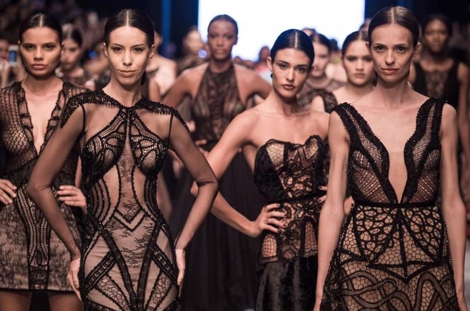 Várias modelos posando em um desfile com vestidos pretos da coleção Oscar Niemeyer de Ivanildo Nunes