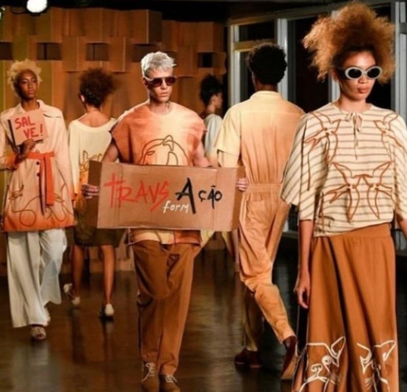 Modelos desfilando para Ronaldo Silvestre com roupas em tom de marrom, branco, laranja e creme, onde se lê uma placa com as palavras TransAção