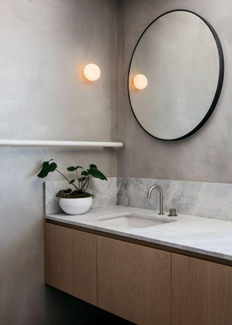 Banheiro com espelho redondo.