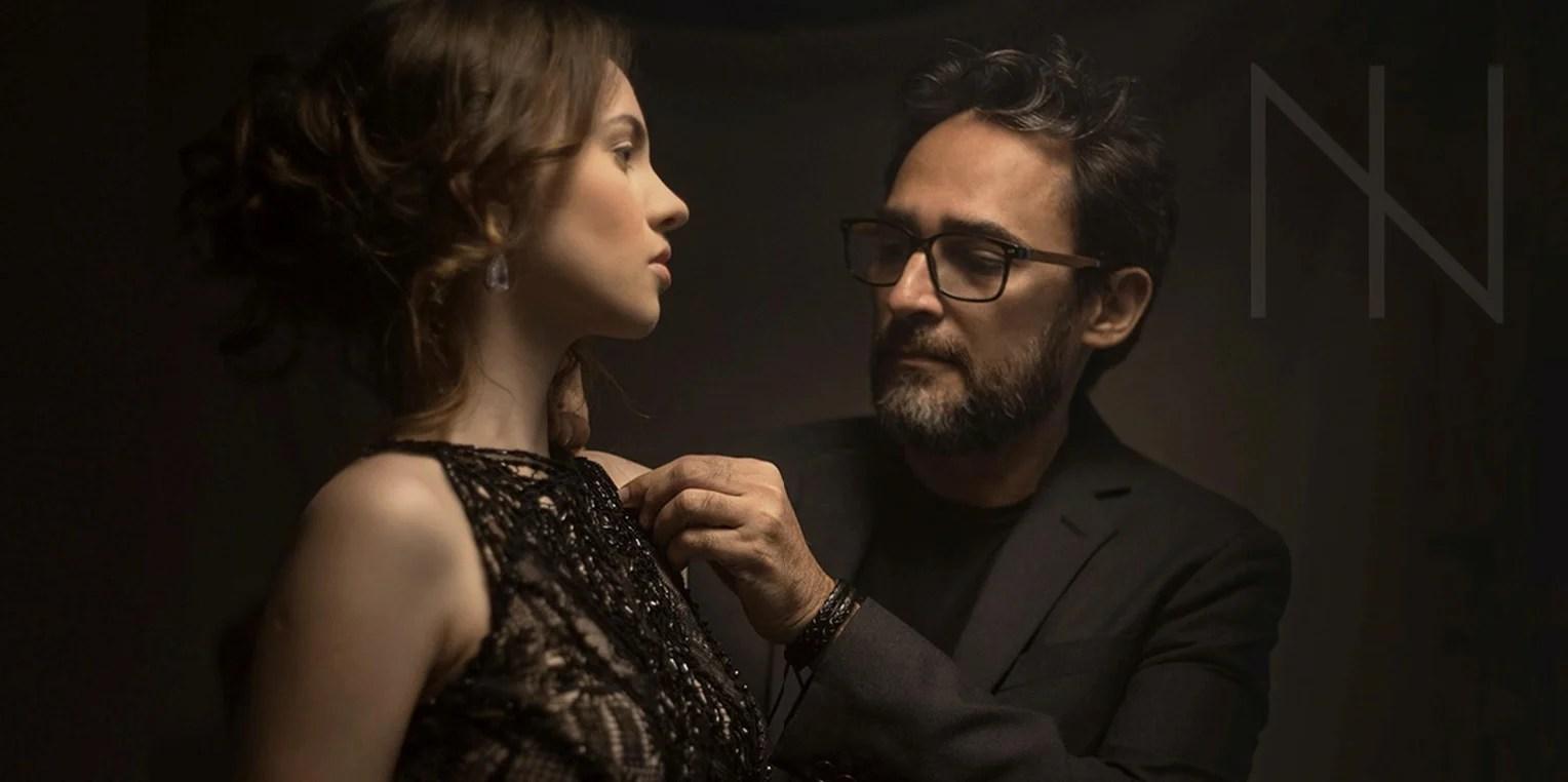 Foto do estilista Ivanildo Nunes posando a ajeitar o vestido de uma modelo, os dois vestidos de preto e em um fundo escuro