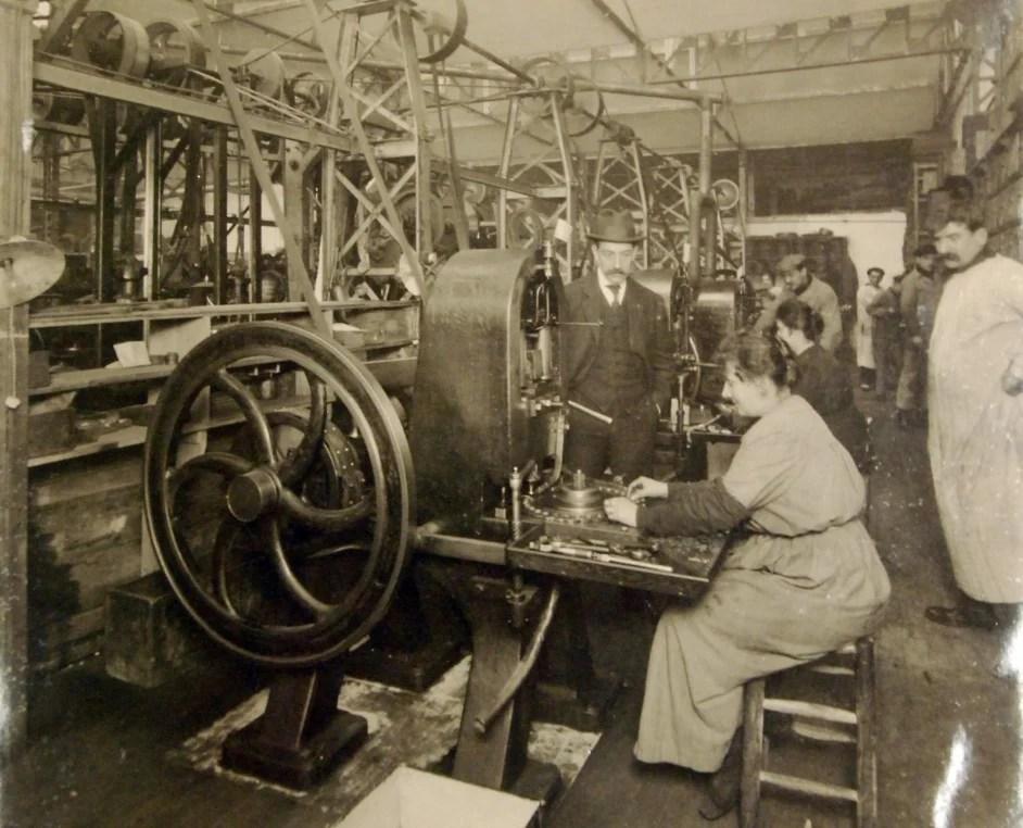 Foto em preto e branco do interior de uma fábrica de botões com uma mulheres sentadas a operar máquina sob a supervisão de homens ao redor