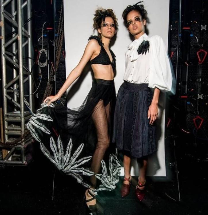 Duas modelos posando em pé com maquiagem preta, uma delas com um top curto e saia transparente preta e a outra com uma camisa branca e saia volumosa preta