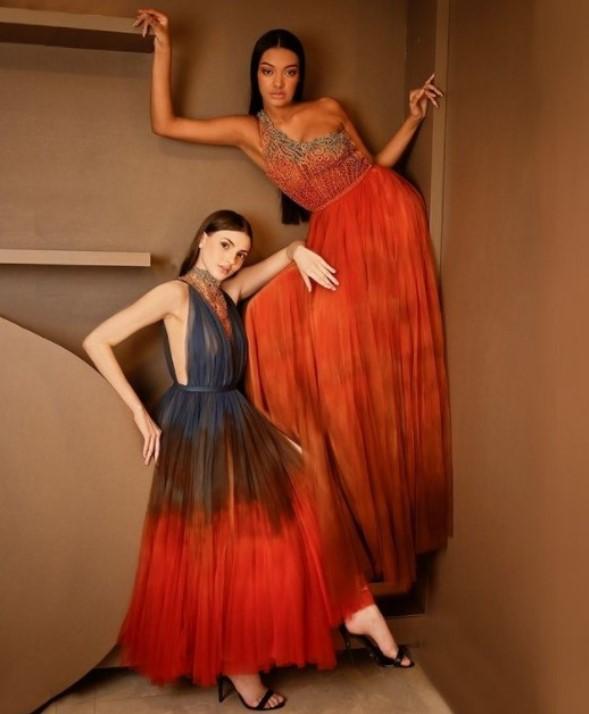 Duas modelos posando contra uma parede com vestidos de festa em tons de laranja e azul do estilista Ivanildo Nunes