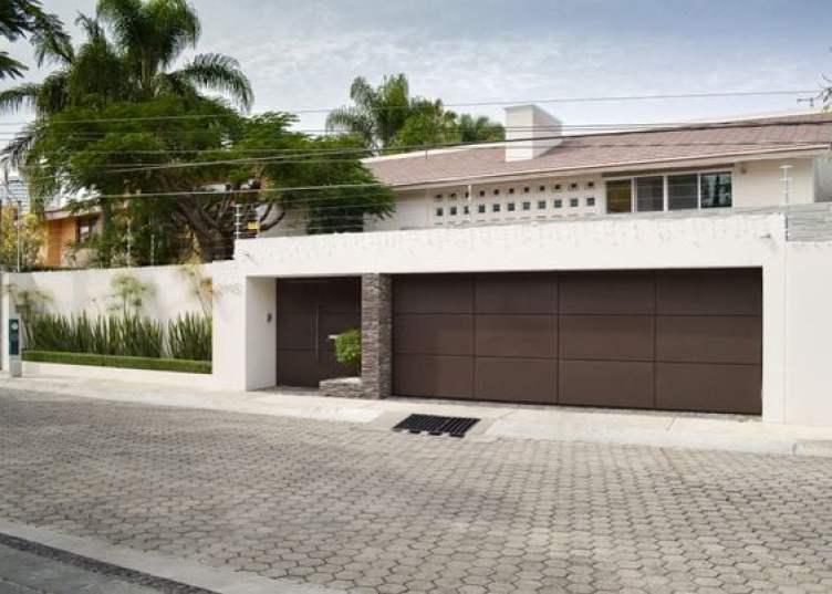 Muro residencial com portões largos marrons.