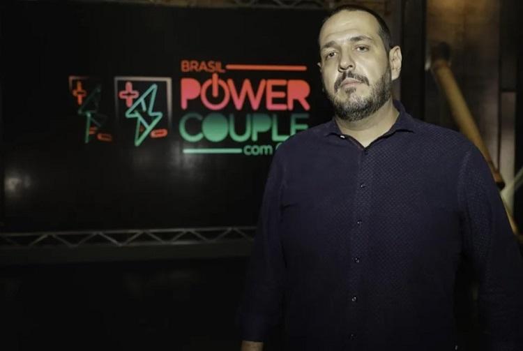 Foto de Fernando Viudez em frente ao logo do reality show Power Couple