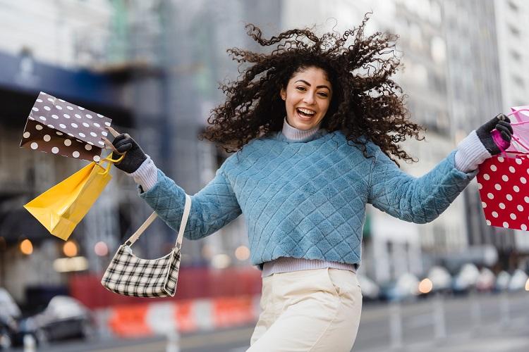 Foto de mulher de suéter azul segurando sacolas de compra