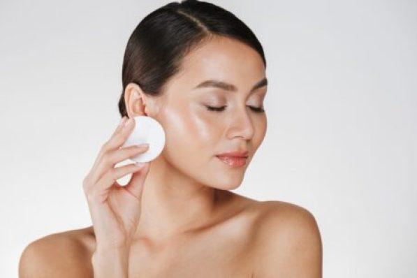 Mulher removendo a maquiagem do rosto com almofada de algodão