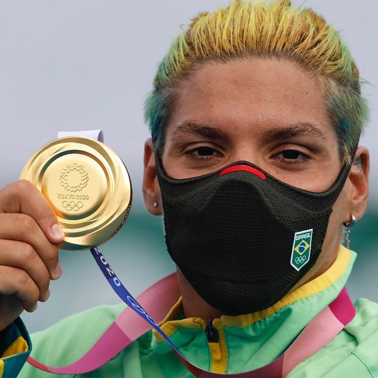 Foto de Ana Marcela segurando medalha de ouro.