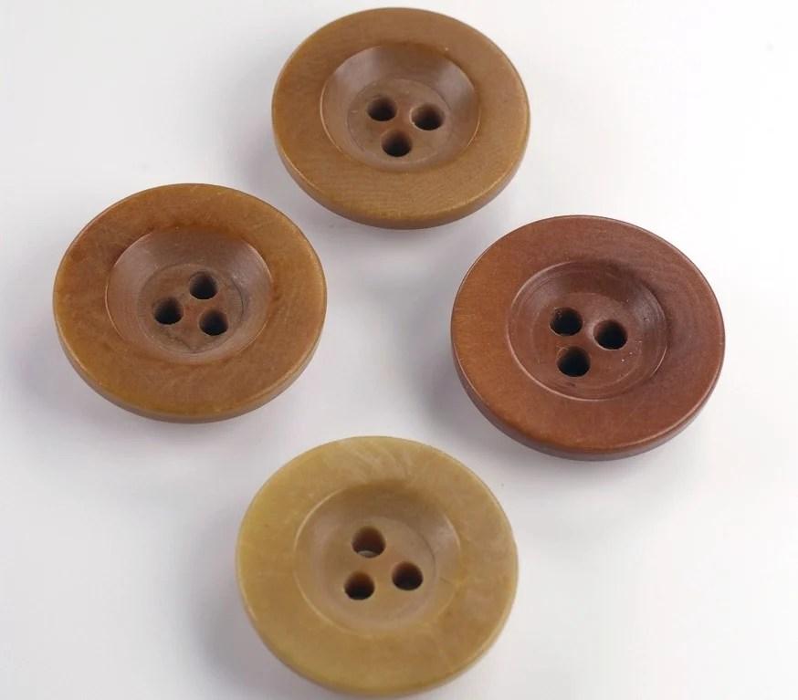 Foto de 4 botões de 3 furos feitos com marfim vegetal em fundo branco
