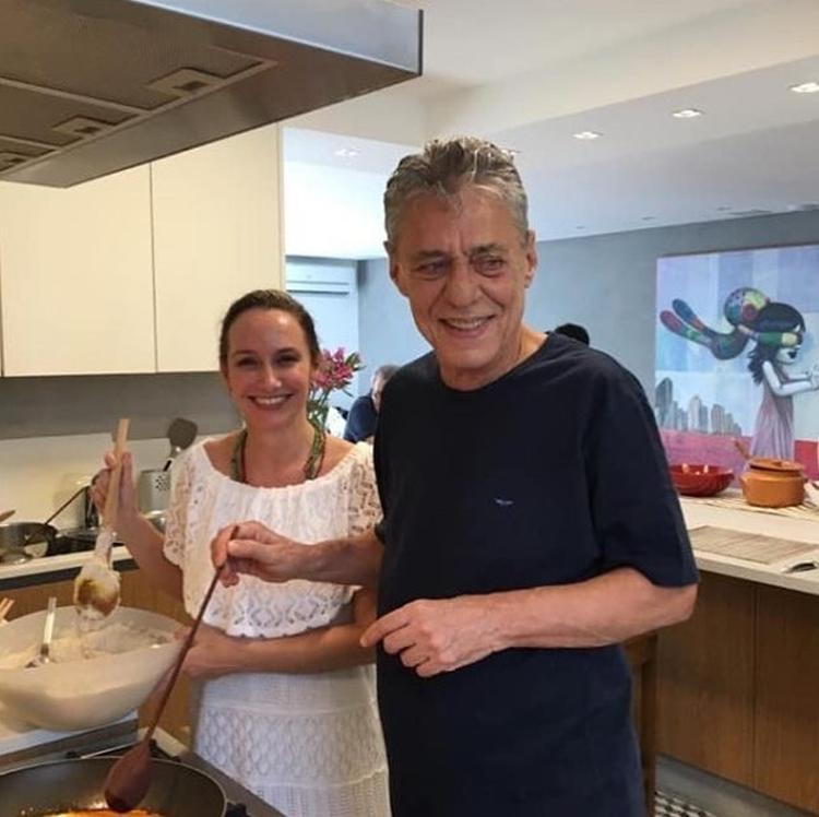 Foto do casal cozinhando.