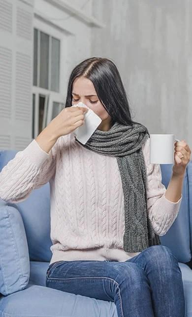 Mulher resfriada assoando o nariz e tomando chá