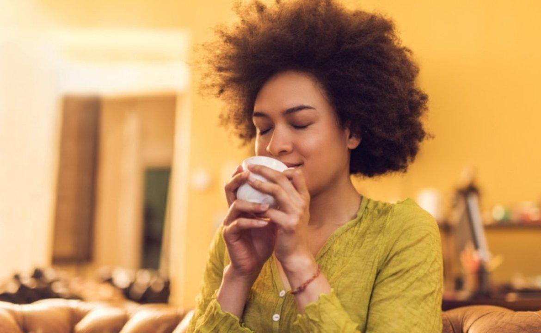 Mulher com os olhos fechados de satisfação tomando chá