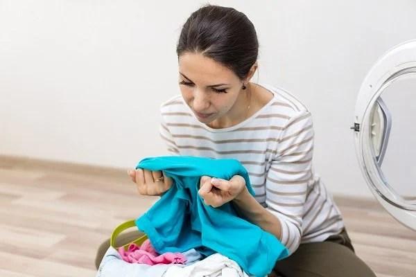 Mulher olhando para roupa manchada de óleo e pensativa