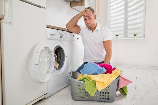 Homem ajoelhado em lavanderia pensativo olhando para as roupas