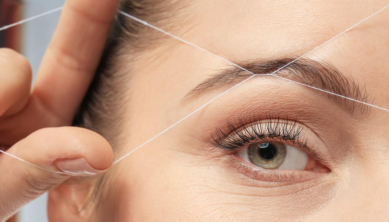 Mulher realizando o método de depilação egípcia na sobrancelha