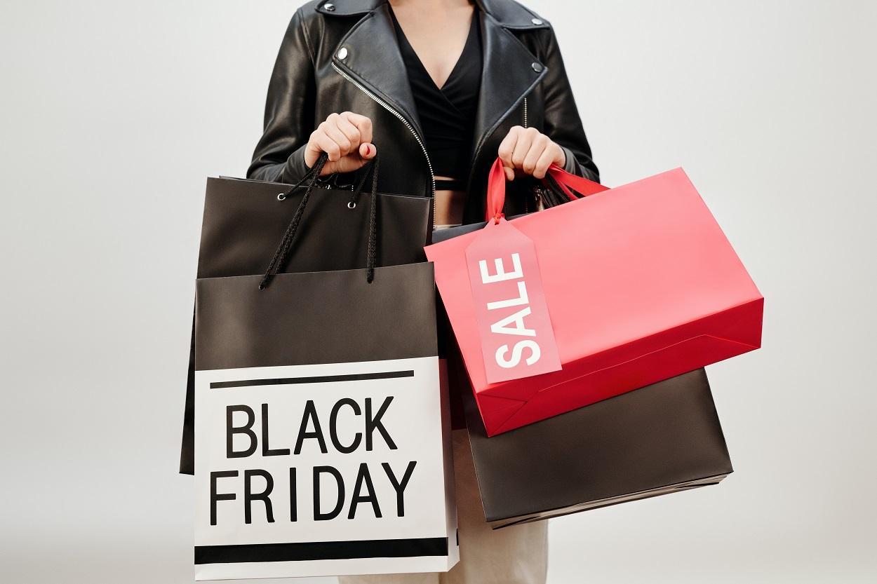 foto de mulher segurando sacolas de compras escrito Black Friday e Sale