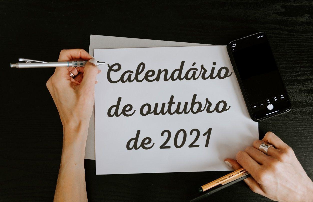 """Foto de mãos de mulher escrevendo """"Calendário de outubro de 2021"""" em uma folha branca usando lapiseira"""