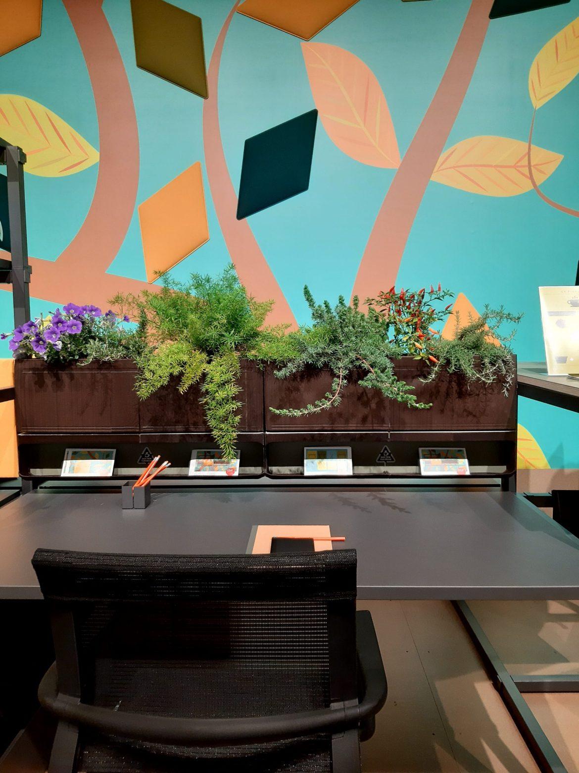 Proposta de home office com jardineira de plantas naturais na parte superior da estação e cadeira ergonômica