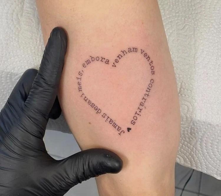 Tatuagem feminina com frase e coração