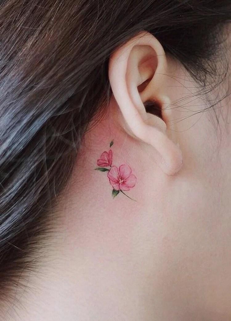 Tatuagem feminina atrás da orelha com flores