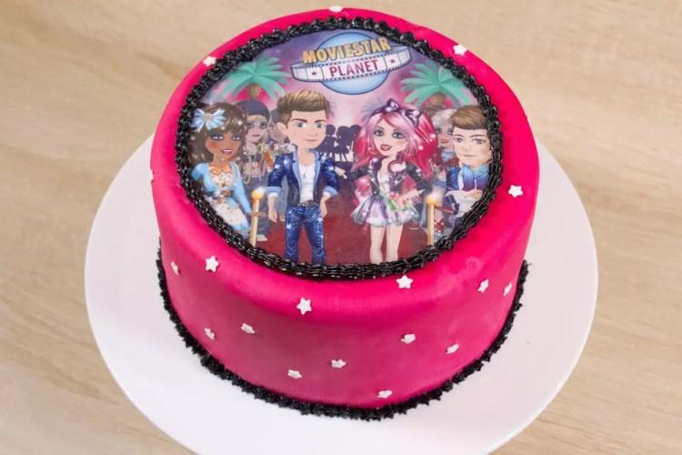 Insertion d'un décor en sucre sur un gâteau – Gâteau Movie Star Planet