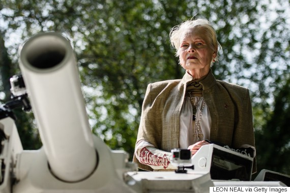 Fashion designer and environmental campaigner Vivienne Westwood rides on top of an armored personnel carrier (APC) towards the home of British Prime Minister David Cameron's home in Chadlington, Oxfordshire on September 11, 2015 to highlight the Government's plan to use hydraulic fracturing (fracking) to recover fossil fuels from the ground in regions of the north of England. The vehicle parked outside the prime minister's home before a group of protestors in gas masks led chants and held banners calling for the Government to change it's policy on the controversial plans.  AFP PHOTO / LEON NEAL        (Photo credit should read LEON NEAL/AFP/Getty Images)