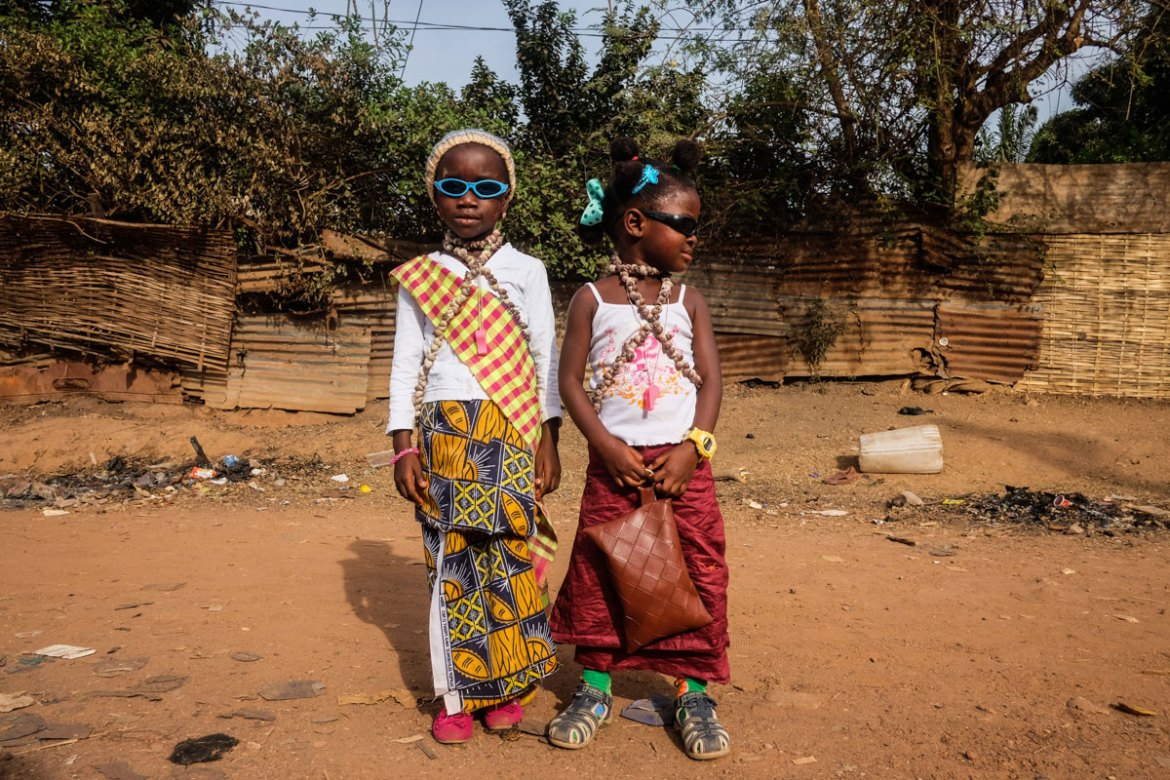 Two girls from the Bijaos ethnic group  show off their carnival outfits and shell necklaces. [Ricci Shryock/Al Jazeera]