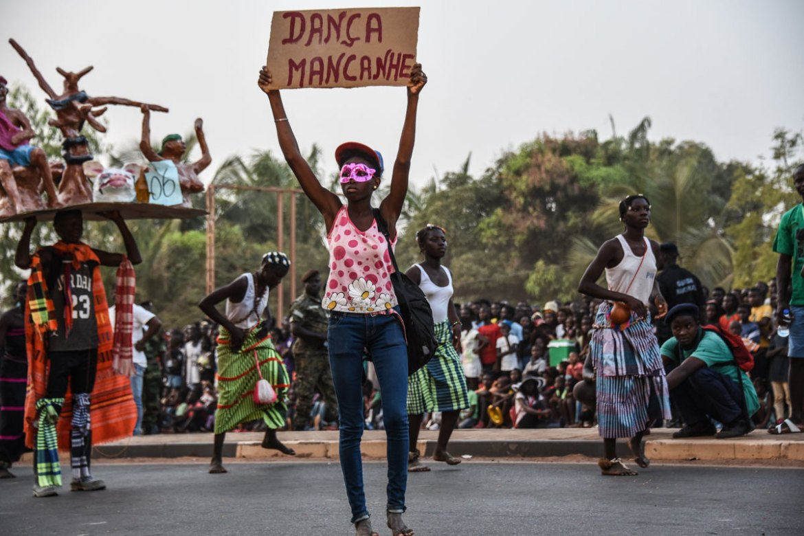 A woman from Bissau holds up a sign announcing her troupe's performance of a 'Mancanhe dance', as they parade down the streets of the capital. [Ricci Shryock/Al Jazeera]