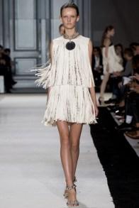 A model wears a fringe-adorned dress for Giambattista Valli's 1970s inspired spring 2015 collection.
