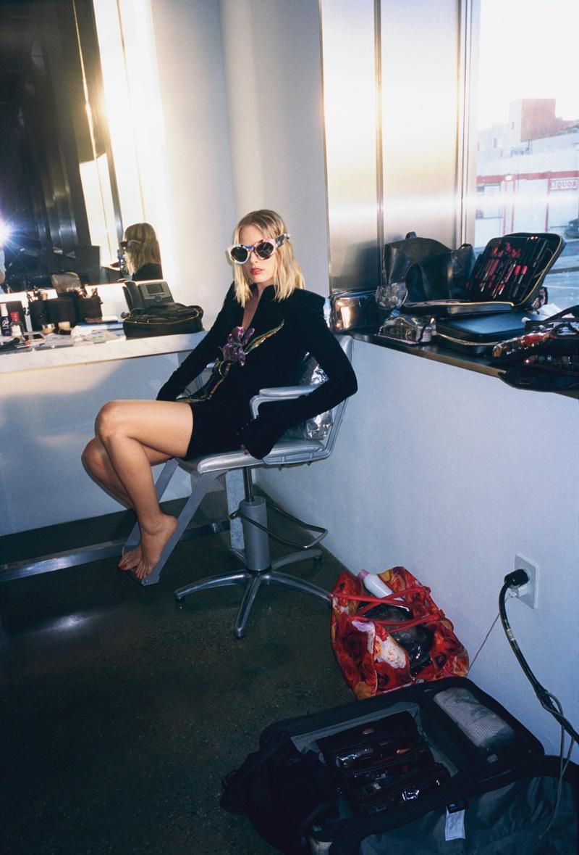 Shot backstage, Margot Robbie wears Saint Laurent dress and Moschino sunglasses