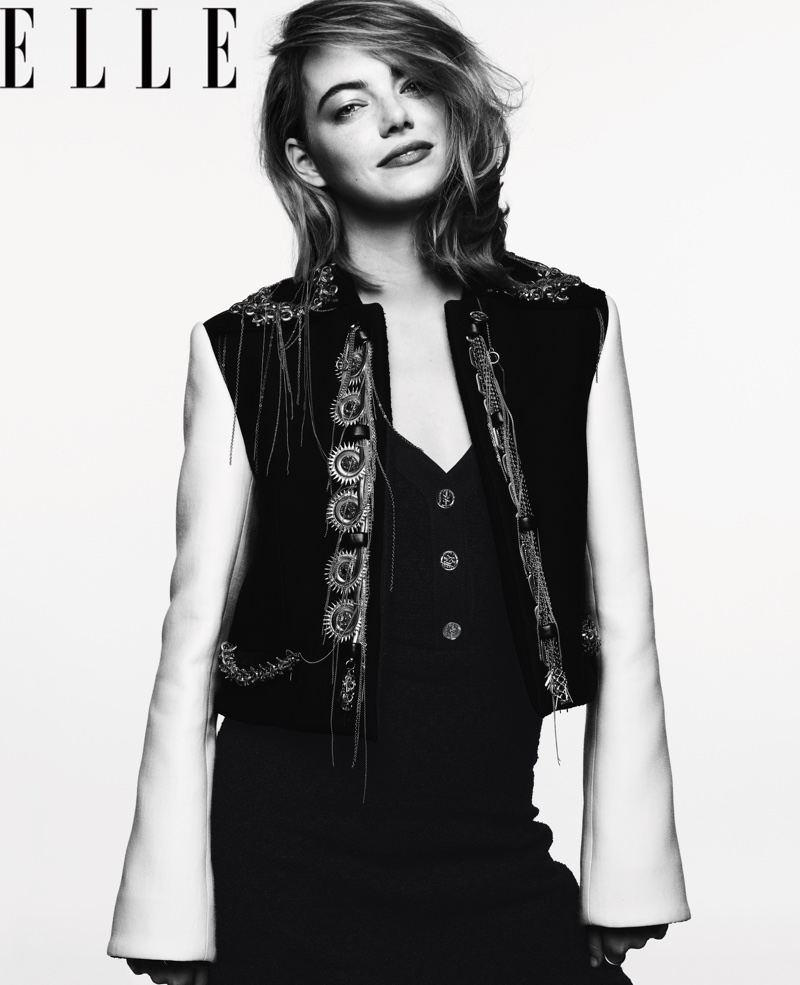 Photographed in black and white, Emma Stone poses in Louis Vuitton jacket and dress
