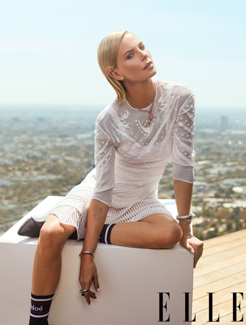 Actress Charlize Theron poses in Chloe white dress, jewelry and knit boots