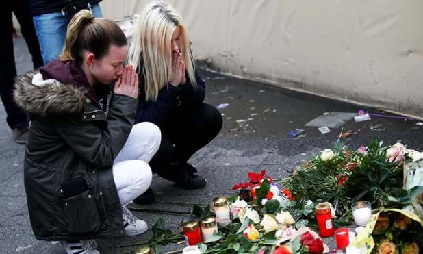 Women mourn at the scene where a truck ploughed into a crowded Christmas market in the German capital last night in Berlin, Christmas Bazaar was Arrested Person not Attack Christmas Bazaar was Arrested Person not Attack The suspect as per Thomas the mystery denied association in the assault